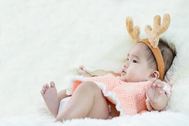 アジアの赤ちゃんとトナカイの衣装の選択的な顔
