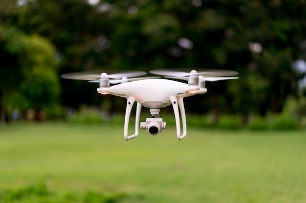 緑の野原を飛ぶ農業無人機