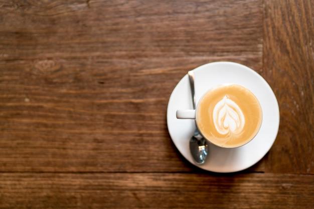 木製のトップビューラテアートコーヒー。ハート形のラテアートフォーム。