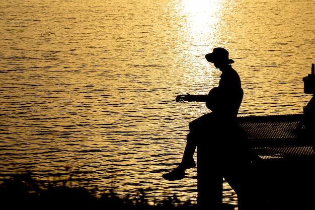夕日の下で川のギターを弾くギタリストのシルエット