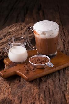 コールドチョコレートミルクドリンクとチョコレートバー、木製の背景