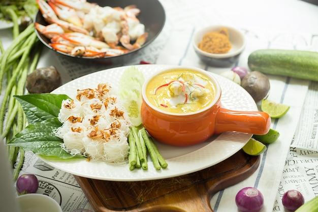 カレーカニ、オレンジのセラミックポットのイエローカレーソースを含むシーフード、テーブルクロスの背景