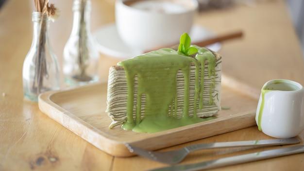 木製のプレートに緑茶の葉と緑茶クレープケーキ。