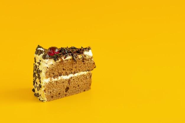 黄色の背景にチョコレートケーキ。コピースペース
