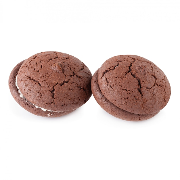 Сэндвич шоколадное печенье и крем на белой тарелке, изолированных на белом фоне