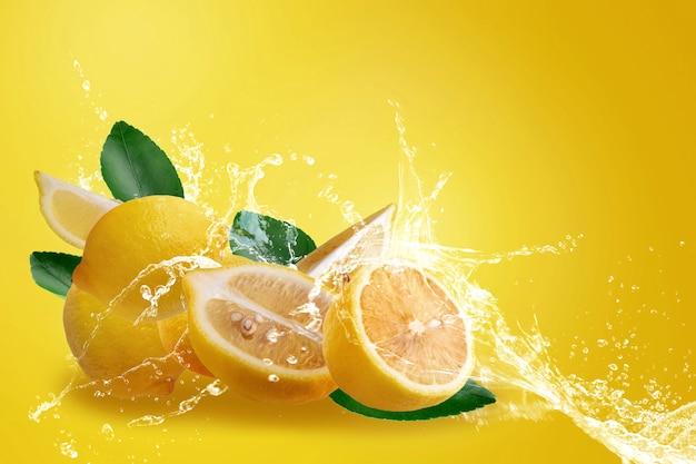 Вода брызгает на свежих нарезанных спелых желтых плодов лимона, изолированных на желтом