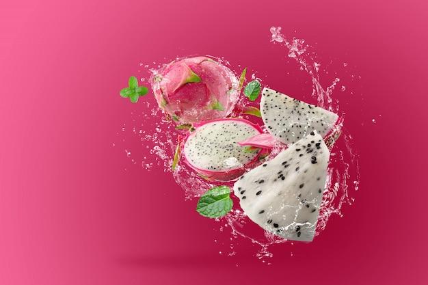 ピンクの背景の上のドラゴンフルーツやピタヤに水しぶき
