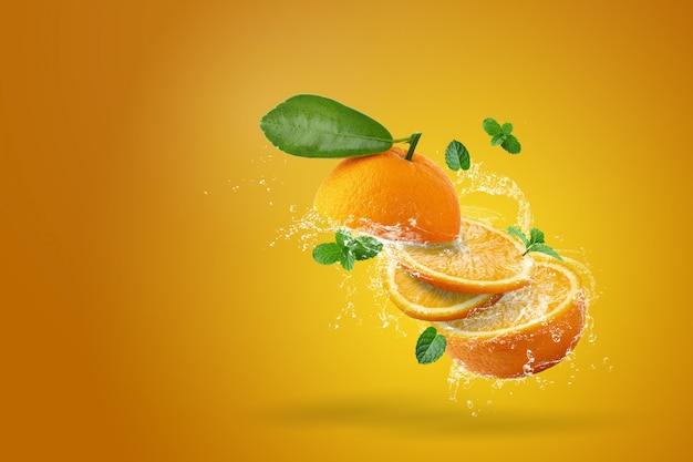 Брызги воды на свежие нарезанные фрукты апельсины на оранжевом фоне