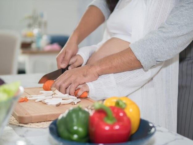 Закройте руки беременной пары приготовления пищи вместе на кухне у себя дома.