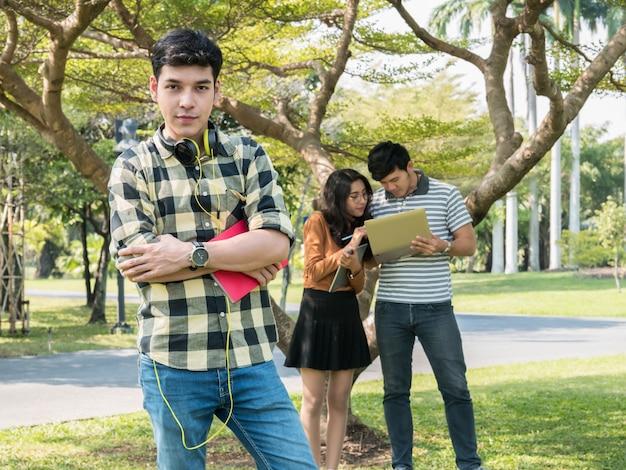 本を持っていると笑みを浮かべてハンサムな若い大学生
