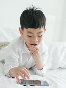 Милый маленький азиатский ребенок сосредоточился на смартфоне лежа на кровати