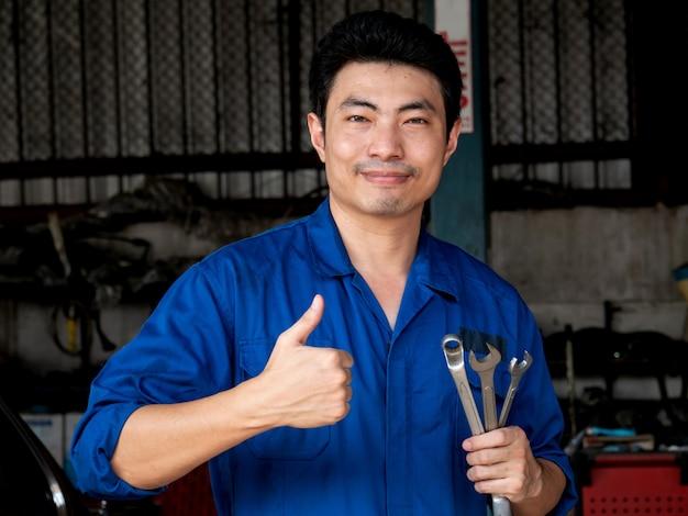レンチを押しながらガレージに親指を現して制服を着た若いアジア自動車整備士。