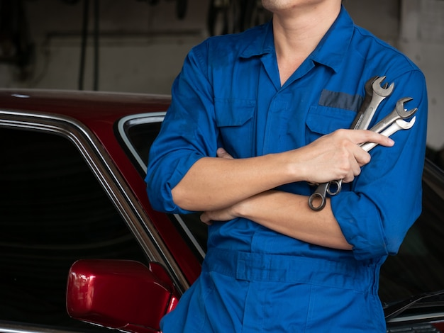 制服保持具やガレージでレンチで自動車整備士のクローズアップ。
