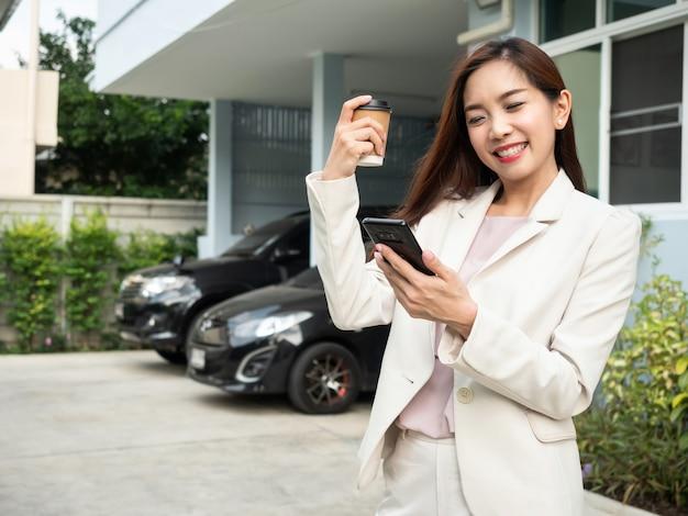 アジアの女性がコーヒーカップを保持していると家の前に立っている間スマートフォンを使用しています。