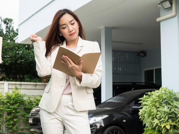 アジアの女性が家の前に立っている間ノートを保持しています。