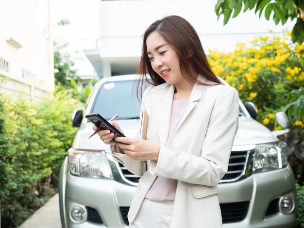 車に対してスマートフォンを使用してアジアの実業家。