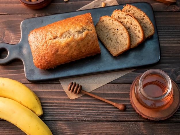 カシューナッツと木製のテーブルの上に蜂蜜とスライスした自家製バナナパンポンド。