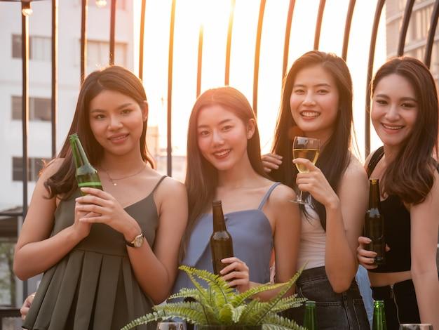 テラスパーティーで応援と飲酒のアジアの友人のグループ。若い人たちが楽しんで、日没で屋上に出かける