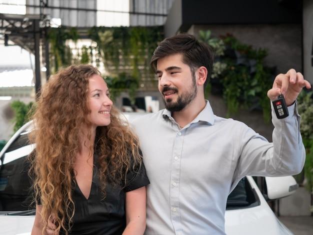 Счастливая молодая милая пара в повседневной одежде обнимает и показывает ключ от машины
