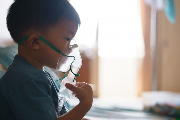 咳を止めるために薬を含む吸入器を使用しているアジアの少年