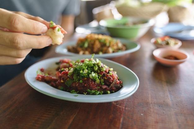 生のスパイシーミンチ肉のサラダを食べる