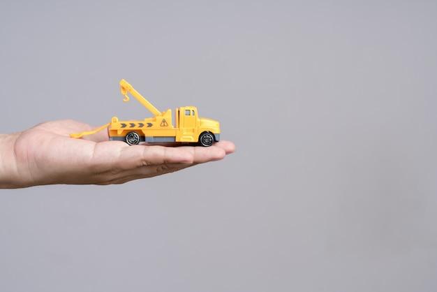 緊急のレッカー車のおもちゃの車を持っている手
