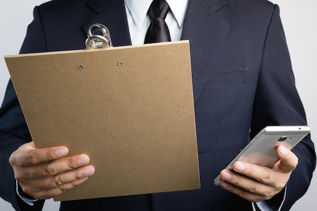 木製のクリップボードを保持し、携帯電話でテキストを入力するビジネスマンの手