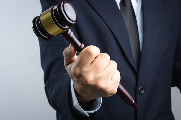 法的または正義のサインとして木製の裁判官の奴隷を持っているビジネスマンの手