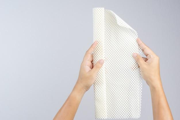 Рука с белым противоскользящим резиновым ковриком для ванной или влажного пола