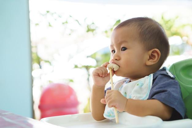 自分で食べるアジアの赤ちゃん