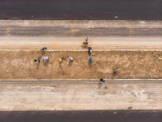 アジア人労働者が泥を水平にするために鍬を使用