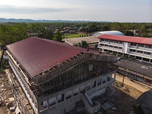 新しいスタジアム屋根を建設するアジア人労働者