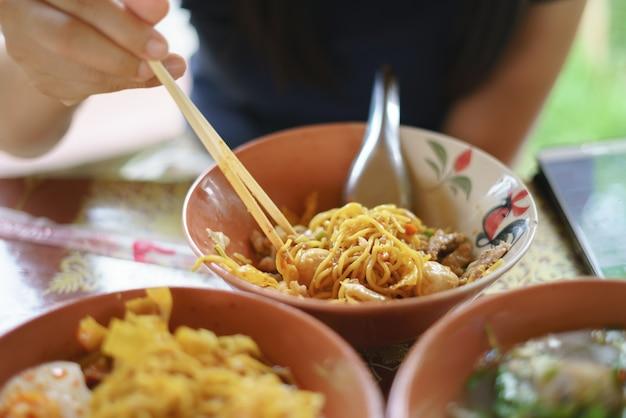 辛くてスパイシーなヌードルを食べるアジア人女性