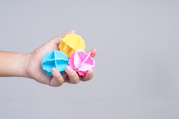 洗濯機のための洗濯プラスチックボールを手に持つ手