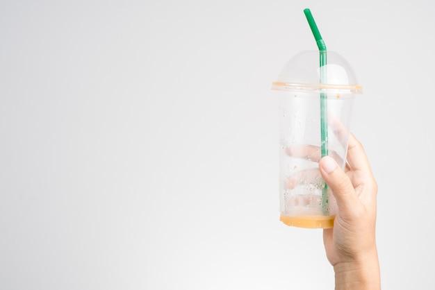 タイのミルクアイスティー、緑のわらの空のプラスチックカップを手に手