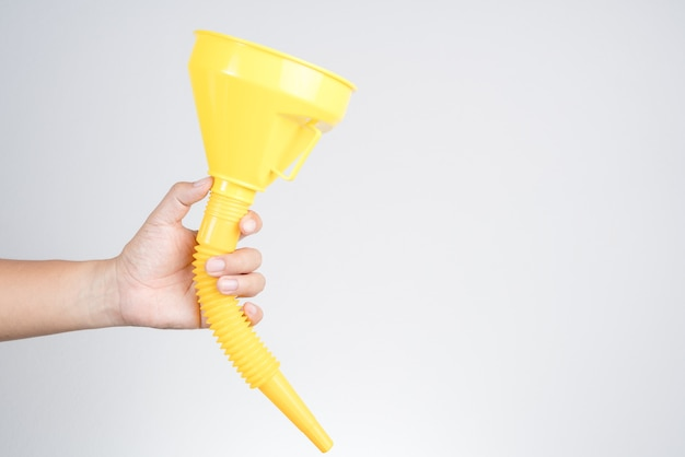 水または流体の移動のための黄色のプラスチック漏斗円錐を保持する手