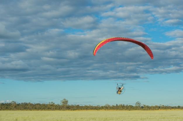 Парамотор пролетает над полями в небе.