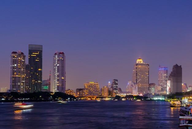 パノラマと超高層ビルの夕暮れのバンコクにあるメーナムチャオプラヤ川