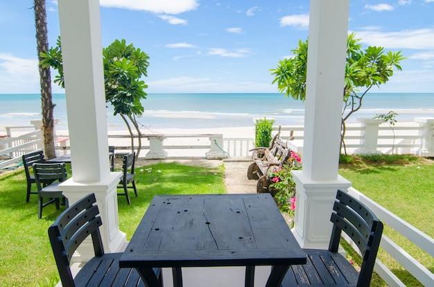 屋外の木製の椅子とテーブルを備えたテラスの海の景色