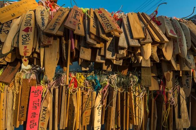 未知の人々と古い木製のサインフェチは幸運のために名前を書いて、願いを作る