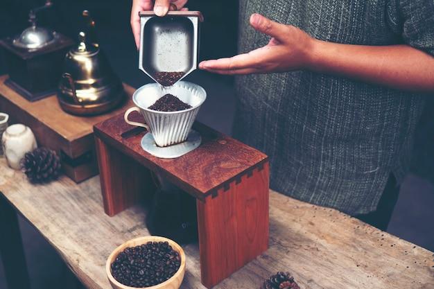 Бариста измельчает кофе с помощью ручной кофемолки.