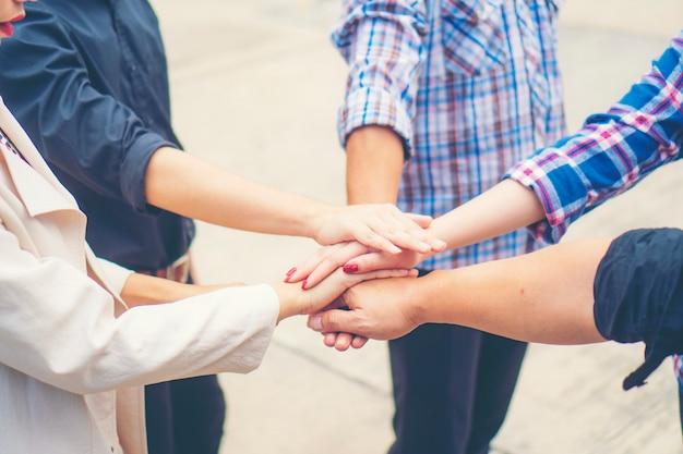 ビジネス人々のグループは勝利のために山に腕を組んだ。手のスタック。協力コンセプト