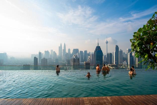 クアラルンプールでの休暇。若い女性は美しい街の景色と屋上プールでの水泳を楽しむ