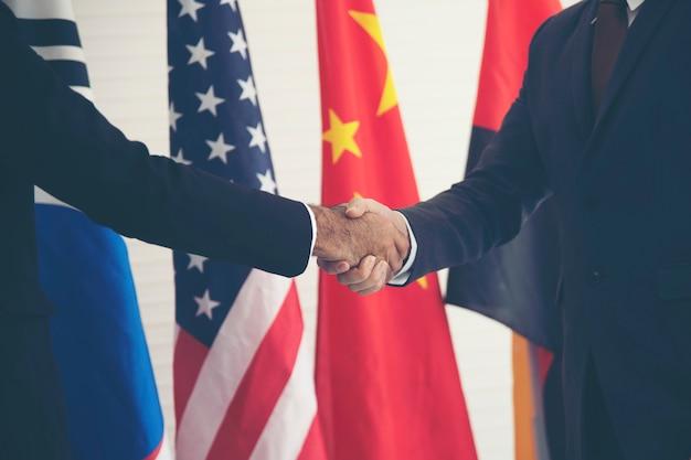 国際的な旗の背景を持つ手を繋いでいるビジネスマン