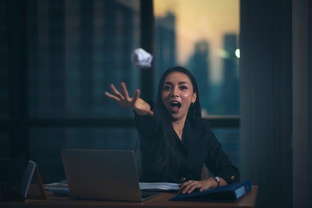 カメラに書類を怒って投げるラップトップと美しい不満ビジネス女性のオフィスの肖像