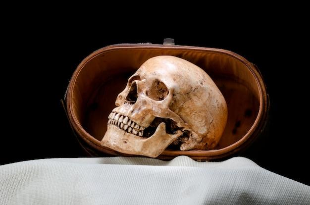 Натюрморт с видом сбоку человеческого черепа на черном фоне