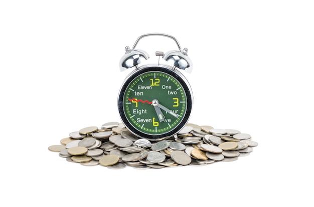 白い背景で隔離のコインと目覚まし時計の立っています。