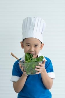 子シェフは新鮮な野菜に満足しています