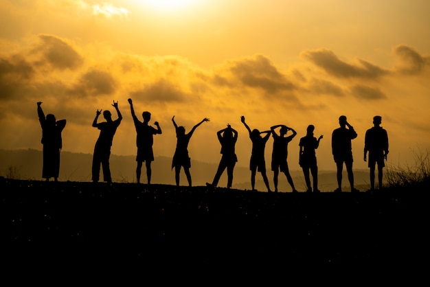 人々のグループのシルエットは丘の上で成功を祝っています。