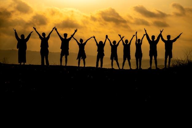 Силуэт группы людей празднует успех на вершине холма.